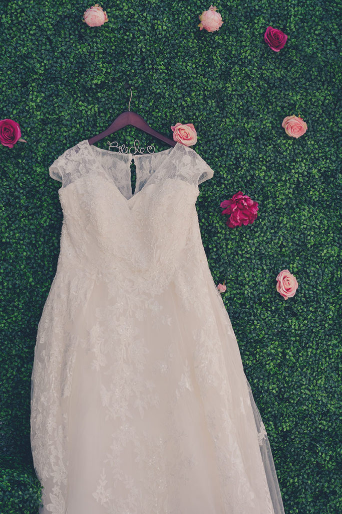 wedding dress hung against a greenery wall backdrop